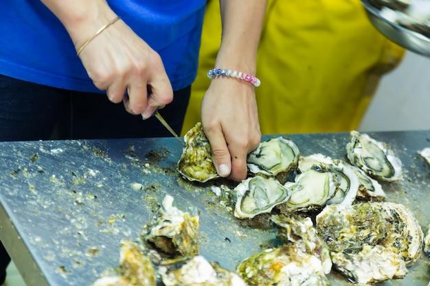 Trabajador abriendo ostras