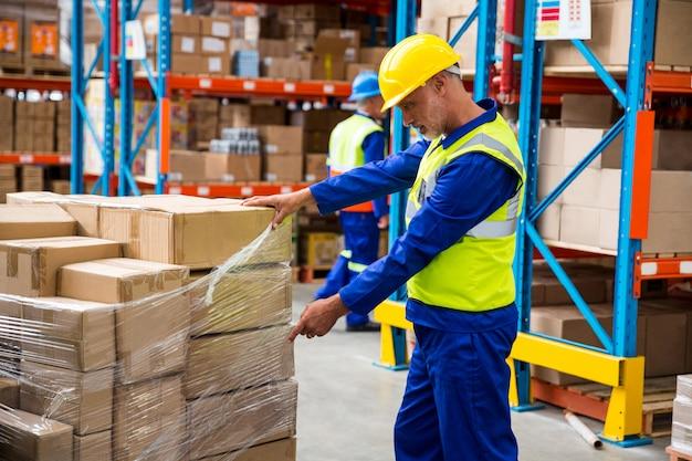 Trabajador abriendo un plástico para las cajas