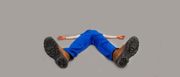 El trabajador se acuesta boca arriba, con las piernas hacia adelante. el hombre agotado o muerto yacía en el suelo. el instalador se desmaya en el piso