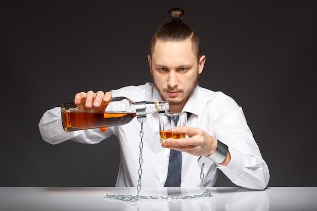 Trabajador adicto sirviéndose un whisky