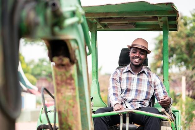 Trabajador africano conduciendo retroexcavadora de equipos de construcción pesada con sonrisa y feliz