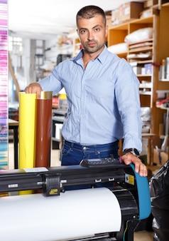 Trabajador de agencia de publicidad masculina con impresión de películas adhesivas