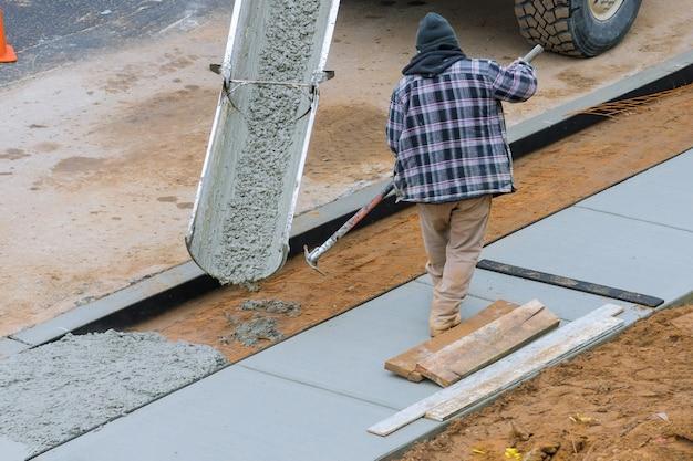 Trabajador de albañil de construcción nivelación de hormigón con hormigón vertido.