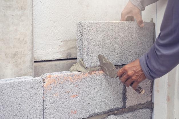 Trabajador de albañil instalando mampostería de ladrillo en la pared exterior con espátula