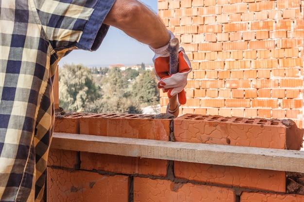 Trabajador de albañil instalando mampostería de ladrillo en la pared exterior con llana