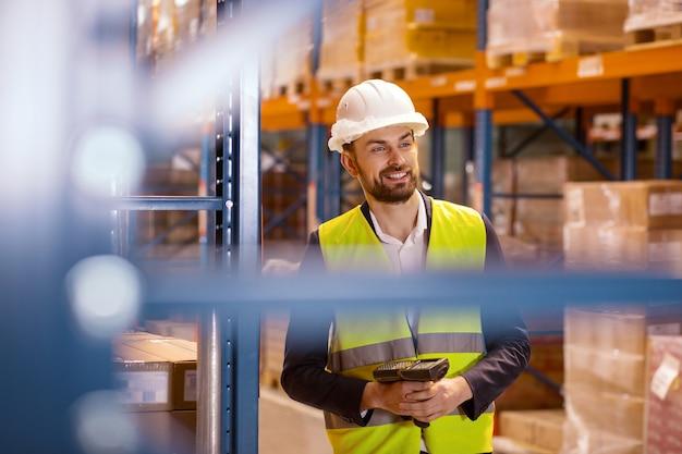 Trabajador de almacén. agradable hombre encantado con un escáner mientras trabajaba en el almacén