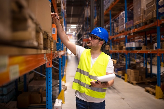 Trabajador de almacén comprobando el inventario en el gran almacén de distribución
