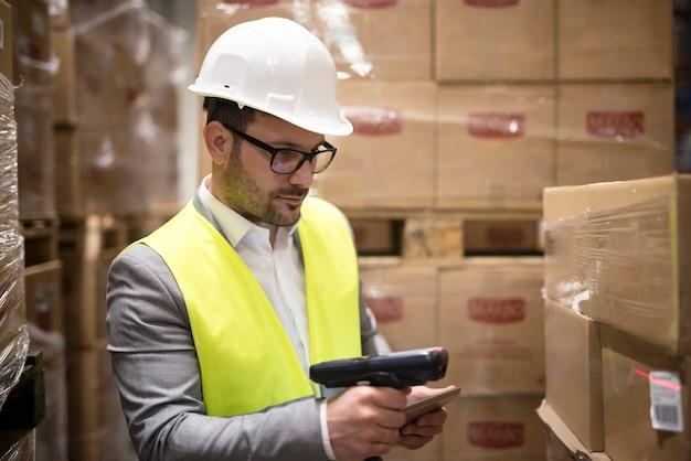 Trabajador de almacén comprobando paquetes con lector de código de barras