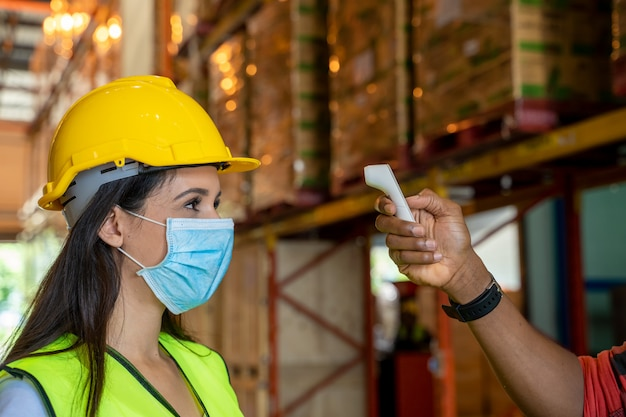 Trabajador de almacén, control de temperatura corporal, prevención de virus conceptos para prevenir enfermedades contagiosas, uso de termómetro infrarrojo médico.