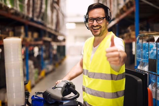 Trabajador del almacén de distribución con auriculares para la comunicación organizando la entrega de mercancías