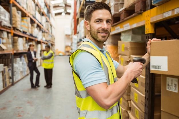 Trabajador de almacén escaneando la caja mientras sonríe a la cámara