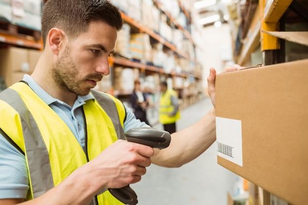 Trabajador de almacén escaneando códigos de barras en cajas