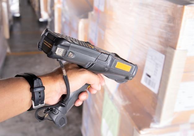 El trabajador del almacén está escaneando el escáner de código de barras con el envío.
