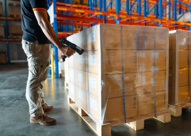 El trabajador del almacén está escaneando el escáner de códigos de barras con paletas de carga en el almacén.