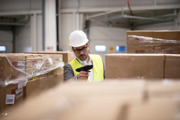 Trabajador de almacén escanear cajas con lector de código de barras en el centro de distribución del almacén