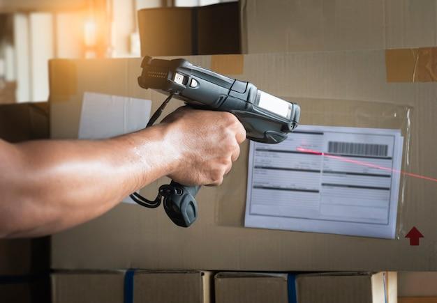 Trabajador de almacén escaneo de escáner de código de barras en la etiqueta de la caja de carga