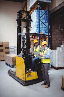Trabajador de almacén hablando con conductor de montacargas en almacén