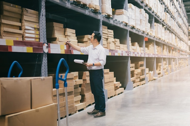 Trabajador del almacén del hombre que comprueba mercancías en el almacén.