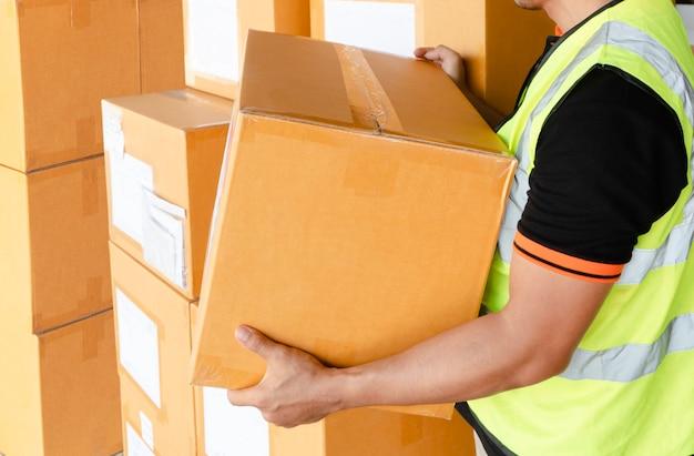 Trabajador de almacén llevando caja de cartón el envío en almacén
