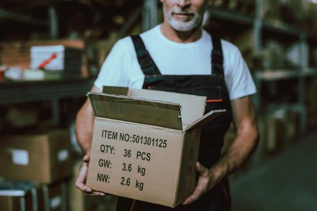 Trabajador de almacén maduro con caja con mercancías