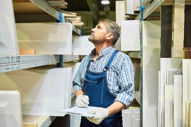Trabajador de almacén maduro haciendo inventario