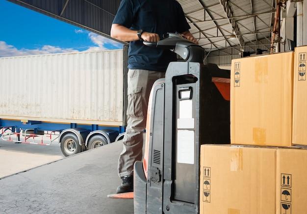Trabajador de almacén manejando carretilla elevadora transpaleta descargando mercancías de paleta