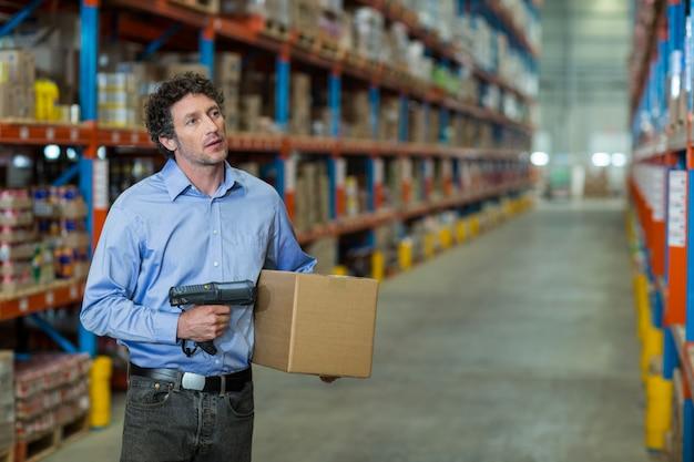 Trabajador de almacén con máquina de escáner de código de barras y caja de cartón