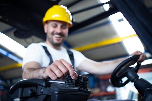 Trabajador de almacén con máquina de montacargas operativa de casco amarillo
