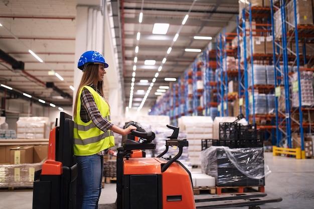 Trabajador del almacén de la mujer que opera la máquina del montacargas en el centro del almacén de distribución grande