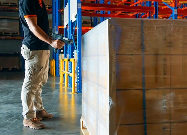 Trabajador del almacén que escanea el código de barras en mercancías de paletas grandes