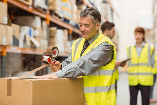 Trabajador de almacén que sella las cajas de cartón para enviar