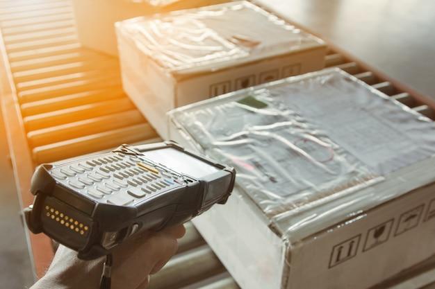 Trabajador de almacén que sostiene el escáner de código de barras con la exploración en cajas del paquete en la banda transportadora