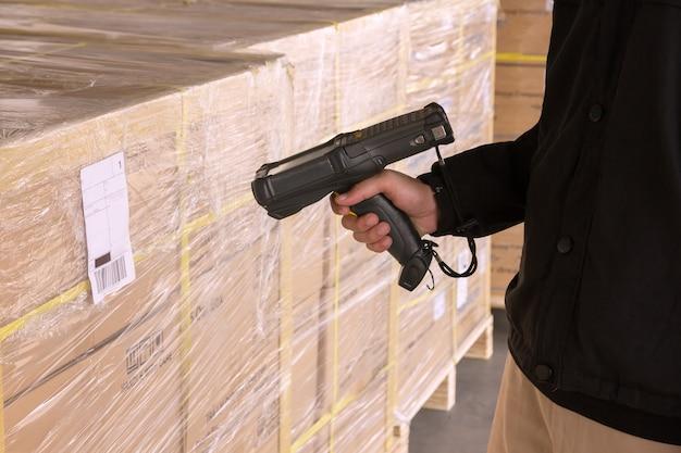 Trabajador de almacén que sostiene el escáner de código de barras con la exploración en un envío de paleta.