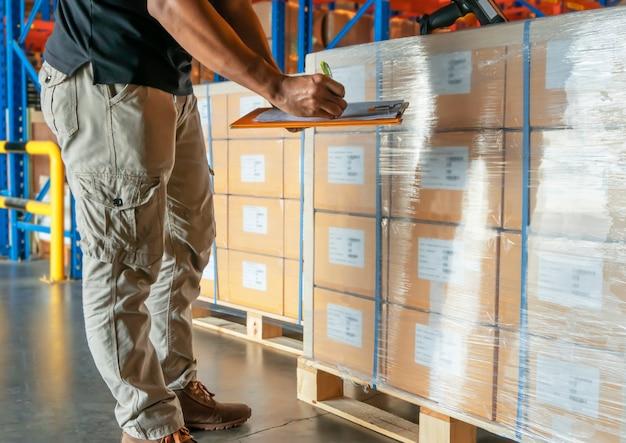 El trabajador del almacén que sostiene el portapapeles es inventario de productos de carga en el almacén.