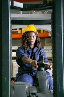 Trabajador de almacén de sexo femenino serio en montacargas operativo casco, mirando al frente