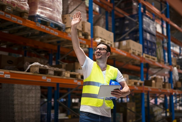 Trabajador de almacén con tableta y uniforme protector de pie entre estantes en el centro de almacenamiento y saludando a su compañero de trabajo