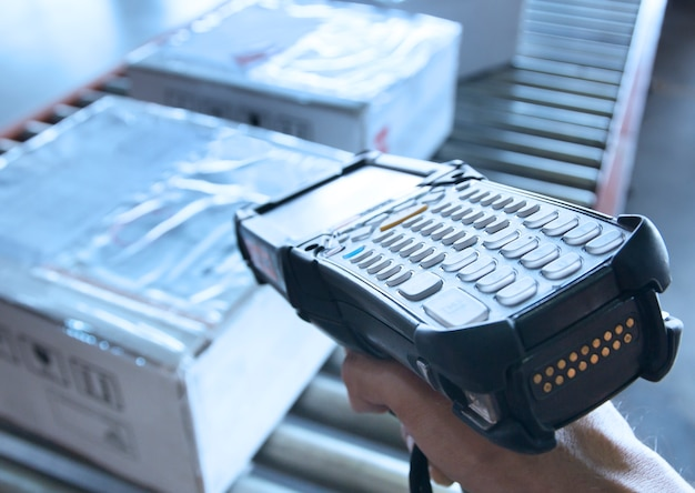 El trabajador de almacén tiene un escáner de código de barras con escaneo en cajas de paquetes