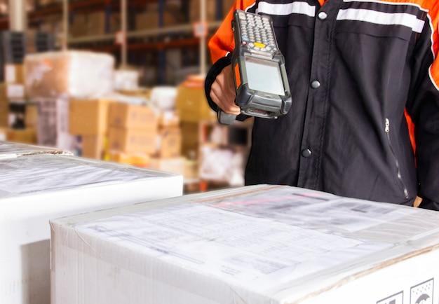 El trabajador del almacén tiene un escáner de código de barras con escaneo láser en una caja de paquetes en la distribución del almacén.