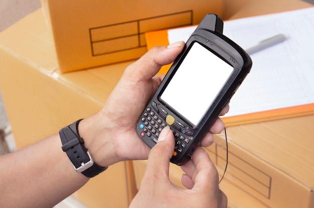 El trabajador del almacén tiene un escáner de código de barras con el inventario de los productos.