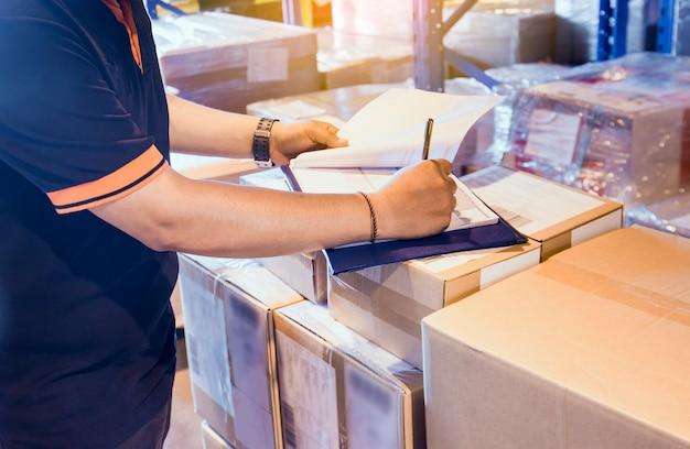 Trabajador de almacén está trabajando en almacén de almacén con inventario del envío.