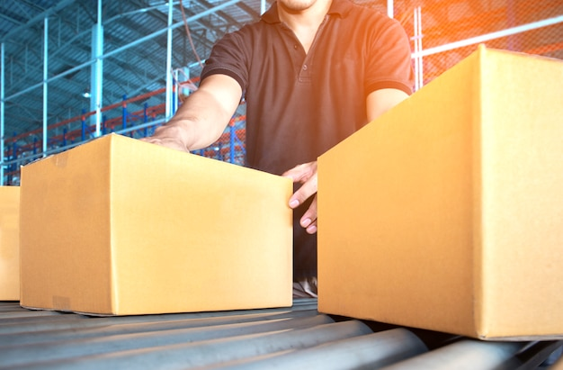 El trabajador del almacén está trabajando con la clasificación de un paquete de cajas en la cinta transportadora.