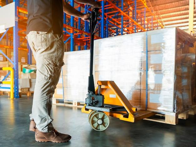 Trabajador de almacén con transpaleta manual descarga carga de envío en el almacén de almacenamiento.