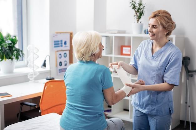 Trabajador amistoso. enfermera amistosa positiva de pie cerca de su paciente mientras le vendar la mano