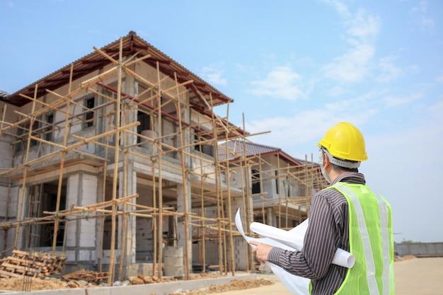 Trabajador de arquitecto ingeniero profesional con casco protector y papel de planos