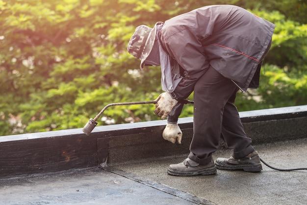 Trabajador de asia que instala la hoja de alquitrán en la azotea