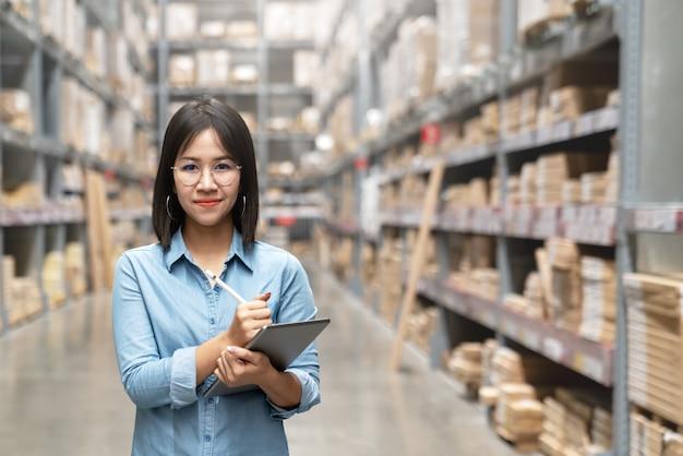 Trabajador asiático atractivo joven, dueño, mujer del empresario que sostiene la tableta elegante que mira la cámara.