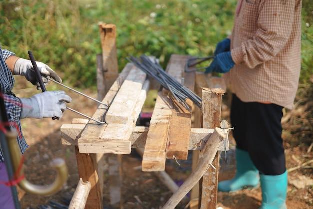 Trabajador asiático doblando metal en el sitio de construcción de la casa
