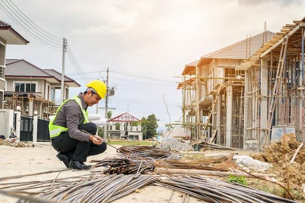 Trabajador asiático del ingeniero de la construcción del hombre de negocios en el casco protector y el papel de los planos en la mano que mira la barra de acero en el sitio de construcción de la casa