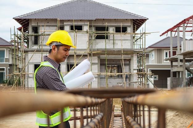 Trabajador asiático del ingeniero de la construcción del hombre de negocios en el casco protector y el papel de planos en la mano que mira la barra de acero en el sitio de construcción de la casa