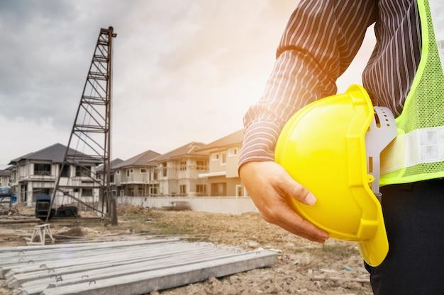 Trabajador asiático del ingeniero de la construcción del hombre de negocios en el casco protector y el papel de los planos en la mano en el sitio de construcción de la casa